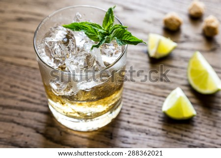Glass of rum on the wooden background - stock photo