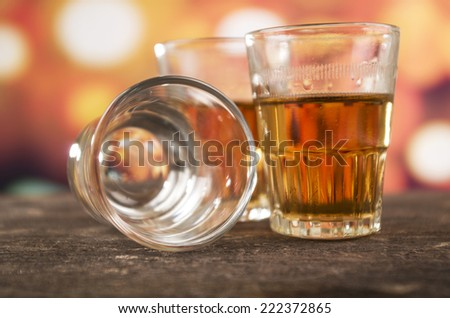 glass of rum whiskey alcohol on wooden table over defocused lights background - stock photo