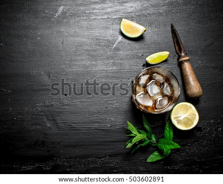 glass of rum with lime and mint. On a black wooden background.