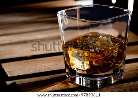 Glass of scotch whiskey and ice on a wooden table - stock photo