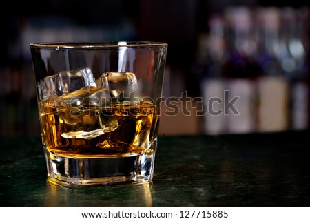 Glass of scotch whiskey and ice on the background of the bar