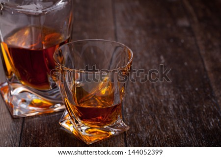 Glass of scotch whiskey on a wooden table - stock photo