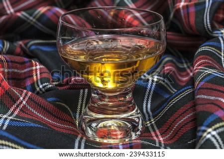 glass of scotch whiskey on scottish cell background - stock photo