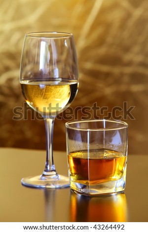 Glass of Scottish whiskey, Glass of white wine - stock photo