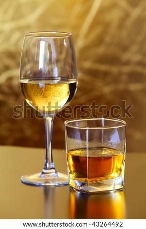 Glass of Scottish whiskey, Glass of white wine - stock photo