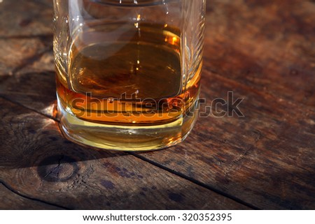 Glass of seasoned whiskey on old wooden surface under sunlight - stock photo