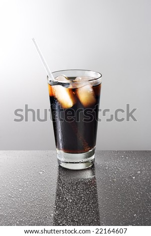Glass of soda on a wet reflective table - stock photo