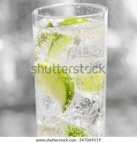 Glass of soda with ice and freshly sliced lime - stock photo
