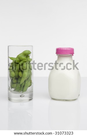 glass of soybeans next to glass jar of milk - stock photo