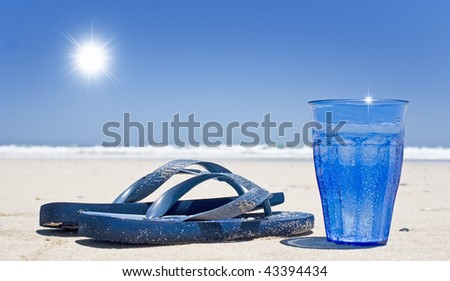 Glass of sparkling water and sandals on the beach with sky and sun - stock photo
