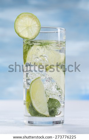 Glass of sparkling water with ice cubes garnished with a slice of lime and mint on blue sky background - stock photo