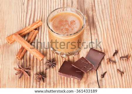 Glass of spiced hot chocolate decorated with cinnamon, cloves and star anise on rustic wooden table with space for text - stock photo