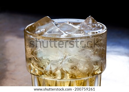 Glass of spirits with ice on a dark background. close-up. up view. - stock photo