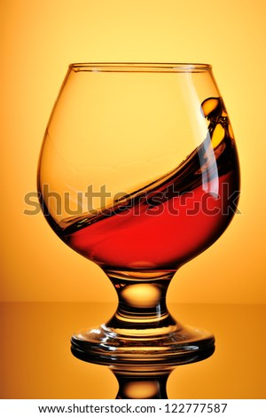 Glass of splash cognac on yellow background