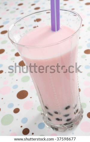 Glass of strawberry flavored pearl milk tea.