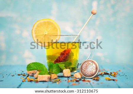 glass of tea with fresh Lemon and mint leaves on blue board