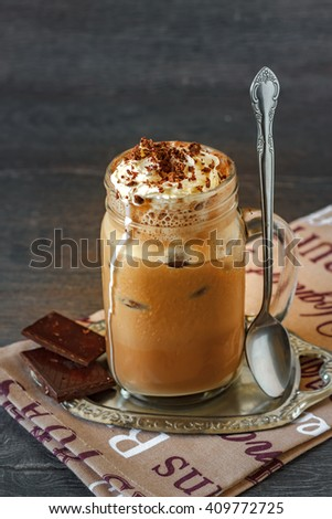 Glass of thick creamy coffee milkshake, frappe or iced coffee with a topping of ice cream and drizzled chocolate - stock photo