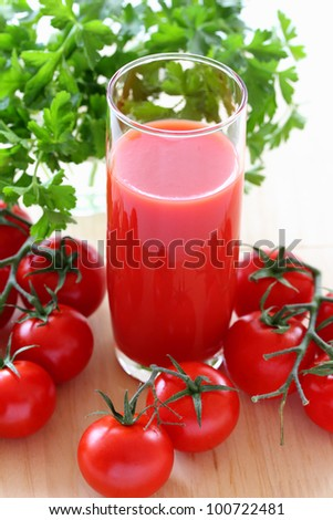 Glass of tomato juice and ripe tomatoes