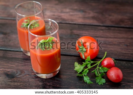 Glass of tomato juice with vegetables on old wooden background, with greenery and tomatoes - stock photo