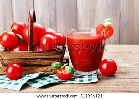 Glass of tomato juice with vegetables on wooden background - stock photo