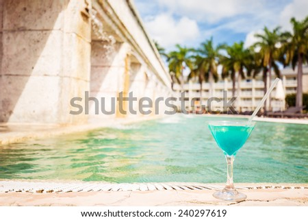 Glass of tropical cocktail on a background of swimming pool of an hotel. Travel, leisure, holiday, paradise getaway, vacation escape, tourism concept - stock photo