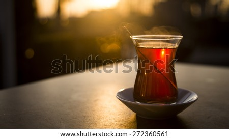 Glass of Turkish tea on the table.Sunset background. - stock photo