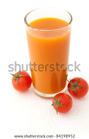 Glass of vegetable juice and fresh tomatoes on white background