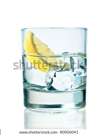 Glass of vodka on the rocks with lemon - stock photo
