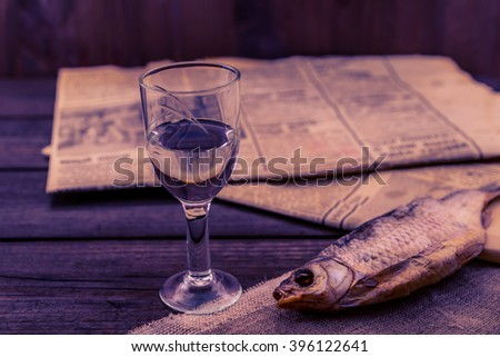 Glass of vodka with a stockfish and newspaper with canvas on an old wooden table. Angle view, shallow depth of field, image in the soft orange-purple toning - stock photo
