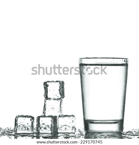 glass of vodka with ice isolaled on white - stock photo