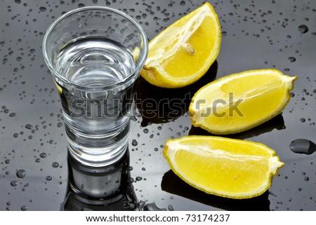 Glass of vodka with lemon sliced - stock photo