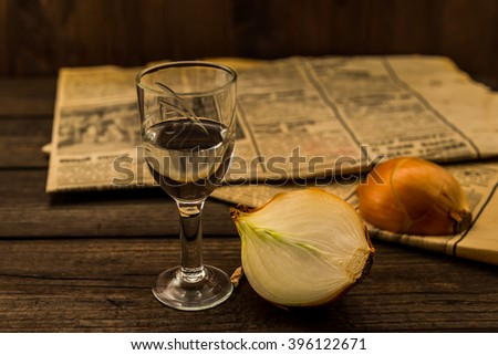 Glass of vodka with newspaper and onion on an old wooden table. Angle view, shallow depth of field - stock photo