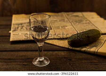 Glass of vodka with newspaper and pickled cucumber on an old wooden table. Angle view, shallow depth of field, focus on the glass of vodka - stock photo