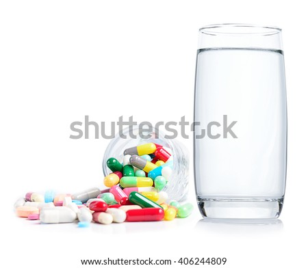 glass of water and medicine pills isolated on white - stock photo