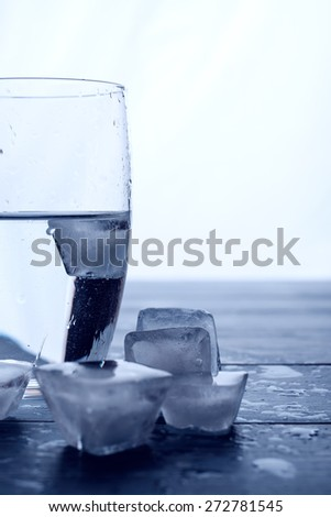Glass of water and melting ice cubes on a wooden table