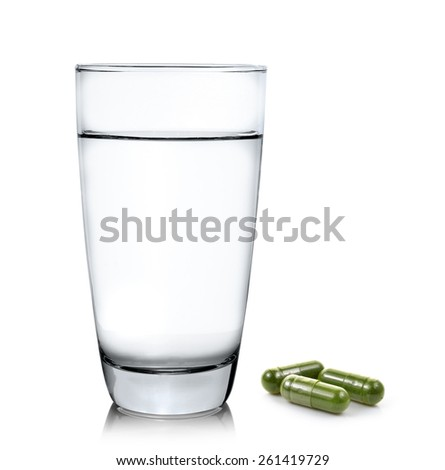 Glass of water and moringa capsule pills on white background - stock photo