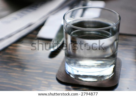 glass of water and paper, half full or half empty? - stock photo