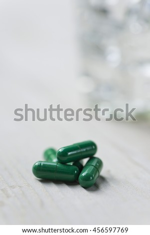Glass of water and pills on white wooden table. Selective focus. - stock photo