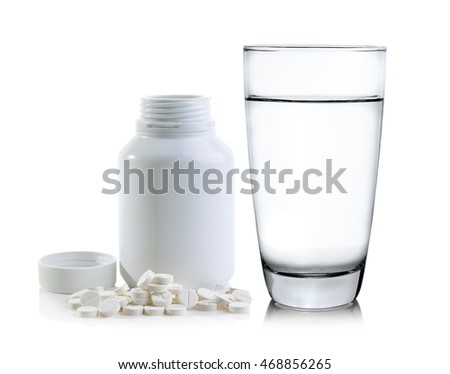 Glass of water and Pills spilling out of pill bottle
