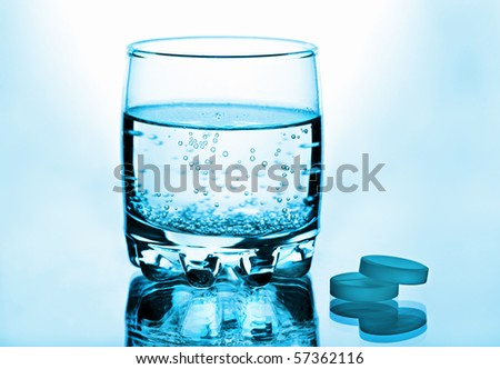 Glass of water and pills toned blue - stock photo
