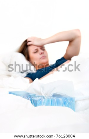 Glass of water and two strips of pills on a bedside table, with a sick woman sleeping in the background. Focus on the glass and strips of pills - stock photo