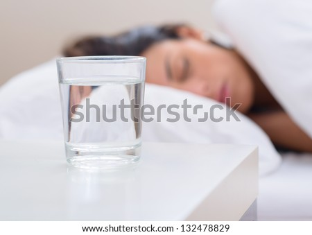 Glass Of Water Beside Bed - stock photo