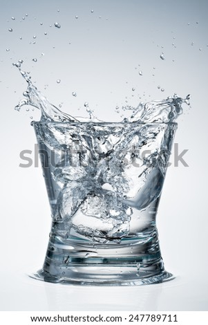 Glass of water. Big splash  with ice. - stock photo
