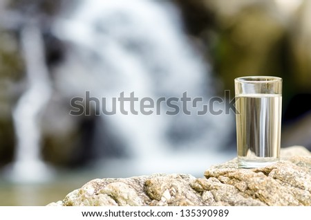 Glass of water by waterfall. - stock photo