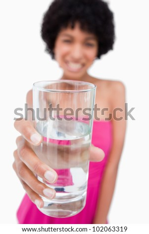 Glass of water held by a beautiful young woman - stock photo