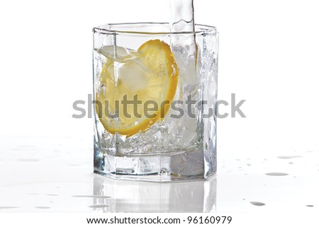 Glass of water, ice and slice of fresh lemon with splash on a white background - stock photo