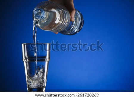 Glass of water in blue background