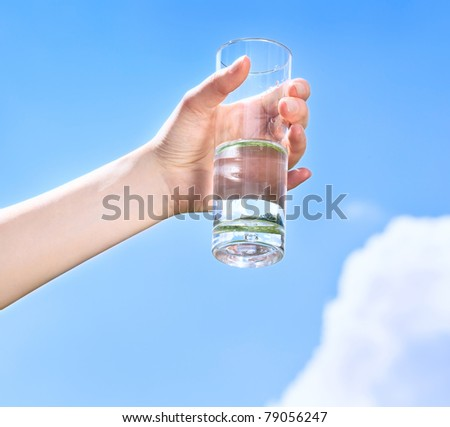 Glass of water in hand on the blue sky with clouds