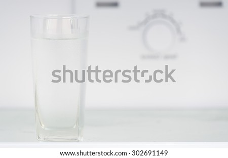 Glass of water in refrigerator  - stock photo