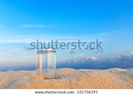 Glass of water is on a coral sandy beach